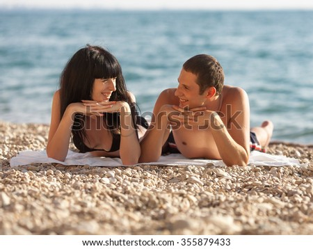 Romantic couple on seashore. Young man and woman lying on beach looking each on other smiling - stock photo