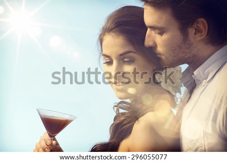 Romantic couple on summer holiday enjoying sunset with a drink. - stock photo