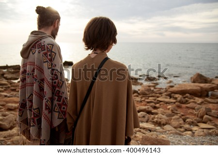 Romantic couple on the beach holding hands watching the sunset. Young men in ponchos against the evening sky. - stock photo