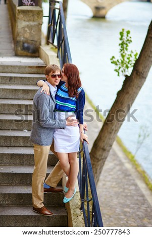 Romantic couple on the stairs at the Seine embankment - stock photo