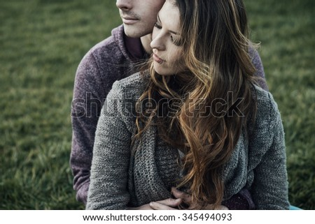 Romantic couple outdoors, they are sitting on grass and hugging, love and relationships concept - stock photo