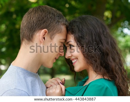 Romantic couple portrait posing in city park, summer season, lovers boy and girl - stock photo