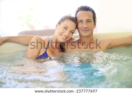 Romantic couple relaxing in hot tub - stock photo