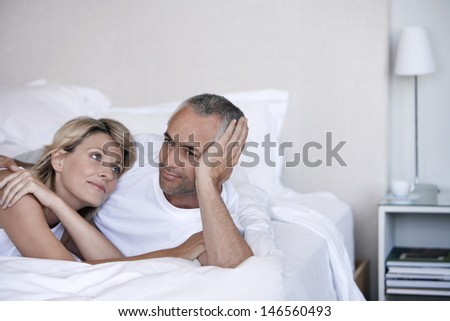 Romantic couple relaxing together on bed in bedroom - stock photo