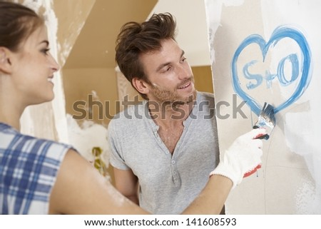 Romantic couple renewing home, painting heart on wall. - stock photo