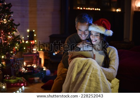 Romantic couple sharing a digital tablet near a wood stove on a winter evening, enjoying the warm christmas atmosphere in their living room,  woman wears a santa hat - stock photo