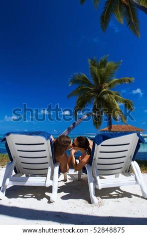 Romantic couple sitting next to palm tree - stock photo