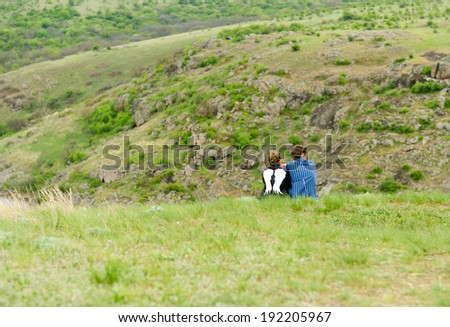 Romantic couple sitting with their backs to the camera on a grassy mountain enjoying the outdoors and the tranquility and solitude of nature - stock photo