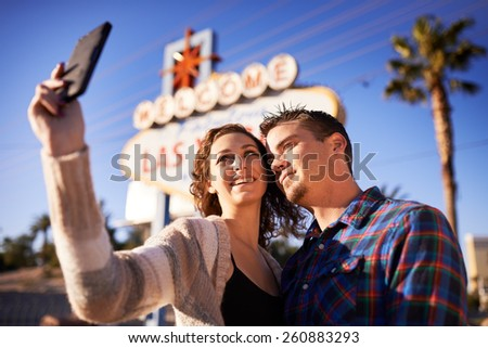 romantic couple taking selfie in front of welcome to las vegas sign - stock photo