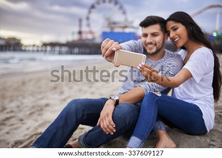 romantic couple taking selfie with phone on beach at santa monica california, shot with selective focus - stock photo