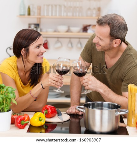 Romantic couple toasting each other in the kitchen with glasses of red wine as they prepare a healthy meal of spaghetti and vegetables together - stock photo