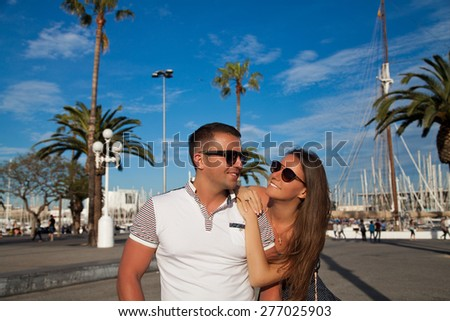 Romantic couple walking outdoors in old harbor, Port Vell in Barcelona Catalonia, Spain. Stylish young man and woman on travel in, Europe. - stock photo