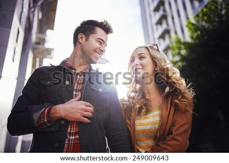 romantic couple walking through downtown los angeles - stock photo