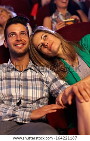 Romantic couple watching movie in cinema, smiling. - stock photo
