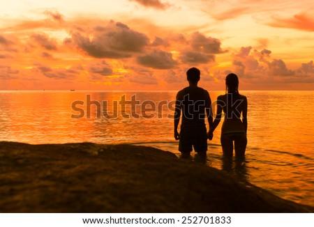 Romantic couple watching sunset at the beach - stock photo
