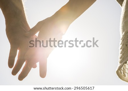 Romantic couple with clasped hands backlit by a bright evening sun in a closeup conceptual image of love, commitment and friendship. - stock photo
