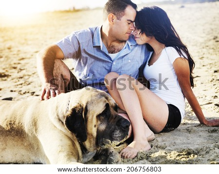 romantic couple with pet dog on the beach. - stock photo