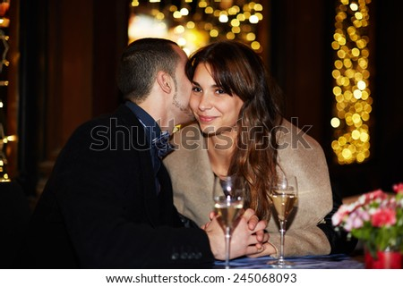 Romantic date at the restaurant, beautiful young couple talking to each other and smiling while spending time at the restaurant together - stock photo