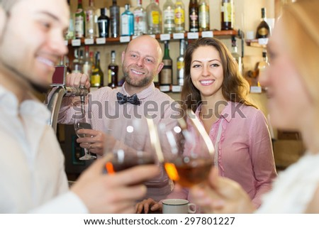 Romantic date of young cheerful couple drinking wine at bar and smiling. Focus on girl - stock photo