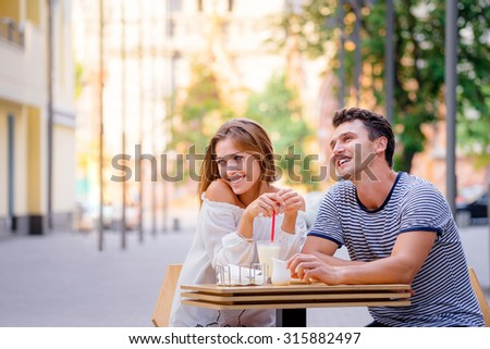 Romantic date. Pretty young loving couple sitting in sidewalk cafe together. - stock photo