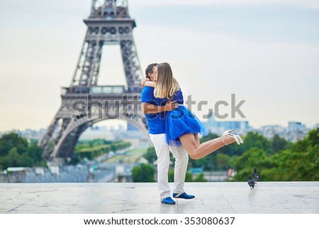 Romantic dating couple on Trocadero viewpoint in Paris, man is rotating his hugged girlfriend around, Eiffel tower is in the background - stock photo