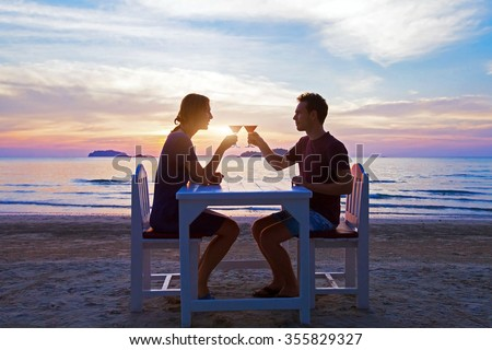 romantic dinner on the beach in luxury restaurant, couple on honeymoon drinking tropical cocktails at sunset - stock photo
