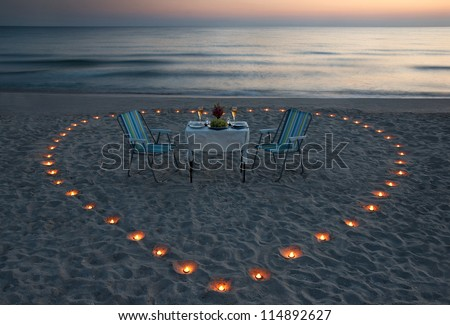 romantic dinner on the sea beach with candle heart in Maldives - stock photo