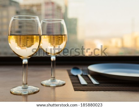 Romantic dinner settings with city view. Glasses of wine with city view. - stock photo