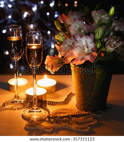 Romantic dinner with bouquet of flowers, candles and champagne glasses. Wedding reception setting. - stock photo