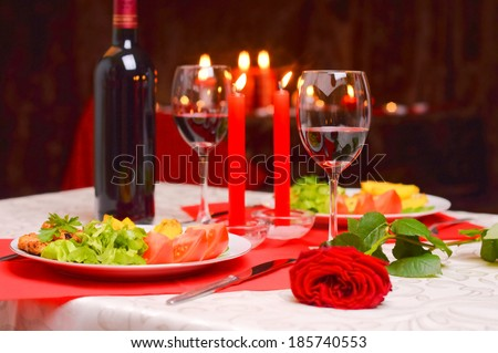 Romantic dinner with wine, candles and a red rose on a table - stock photo