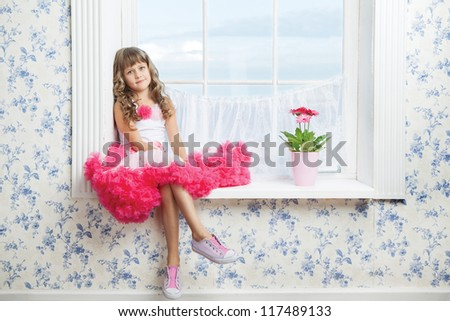 Romantic dreaming young girl dressed luxuriant wavy ball dress with frill sitting on white windowsill inside room near fresh natural flower in flowerpot - stock photo