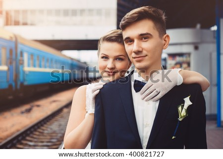 Romantic embrace of newlyweds. Groom and bride are embracing and looking at camera.Couple are smiling, they are happy. The bride put her hands on the shoulders of the groom. Newlyweds in love.  - stock photo