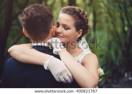 Romantic embrace of newlyweds. Groom and bride are embracing.  The bride put her hands on the shoulders of the groom. Newlyweds in love. They became husband and wife this day. - stock photo