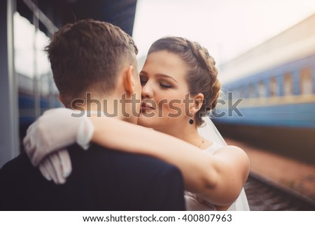 Romantic embrace of newlyweds. Groom and bride are kissing. Bride is smiling, she happy. The bride put her hands on the shoulders of the groom. Newlyweds in love. - stock photo