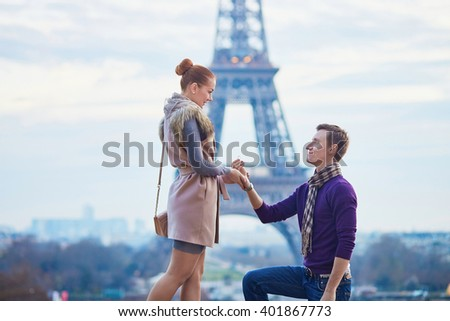 Romantic engagement in Paris, man proposing to his beautiful girlfriend near the Eiffel tower - stock photo