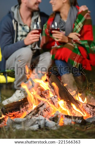 Romantic evening. Charming couple near a fire while camping drinking wine - stock photo