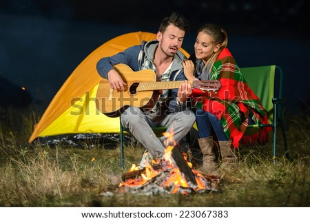 Romantic evening. Couple campfire while camping. playing guitar - stock photo
