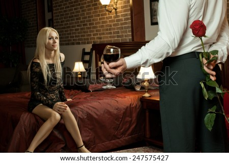 romantic evening date in hotel room, guy with  sexy girl on bed - stock photo