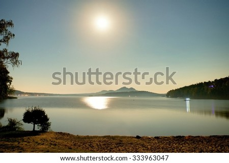 Romantic full moon night at lake, calm water level with moon rays - stock photo