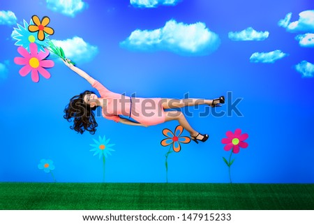 Romantic girl is flying through the sky on flowers. - stock photo