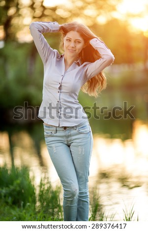 Romantic girl outdoors enjoying nature Beautiful Model in Casual jeans in sun light Long healthy Hair  Backlit Warm Color Tones Beauty Sunshine woman Smiling Sunny Summer Day Autumn Summertime Glow - stock photo
