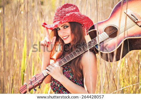 Romantic girl traveling with her guitar. Summer. Hippie style. - stock photo