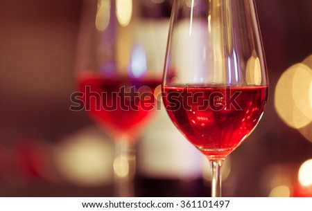 Romantic glass of wine setting by the beach against a colorful sunset. - stock photo