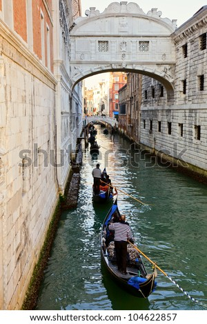 Romantic gondola cruise through the canals of Venice in evening light - stock photo