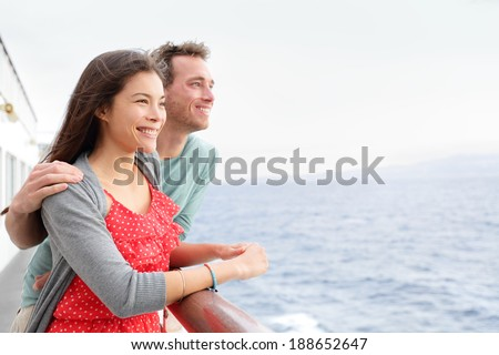Romantic happy couple on cruise ship on boat travel embracing looking at view. Happy lovers traveling on vacation sailing on open sea ocean enjoying romance. Young Asian woman and Caucasian man. - stock photo