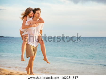 Romantic happy couple on the beach at sunset, man and woman in love - stock photo