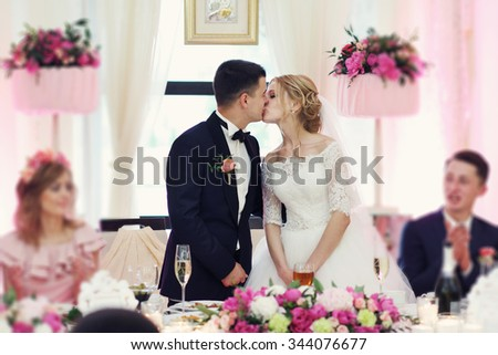 Romantic happy handsome groom kissing beautiful white dress bride at wedding reception - stock photo
