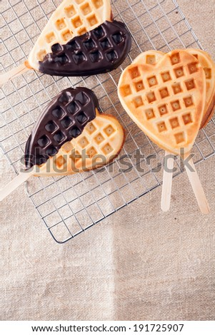 Romantic heart shaped waffle lollipops with a crisp golden wafer dipped on one side in dark chocolate cooling on a wire tray in a kitchen for Valentines or an anniversary - stock photo
