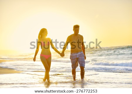 Romantic honeymoon couple in love holding hands walking on beautiful sunset at beach in waterfront. Lovers or newlywed married young couple by the sea enjoying vacation travel holiday. Oahu Hawaii USA - stock photo
