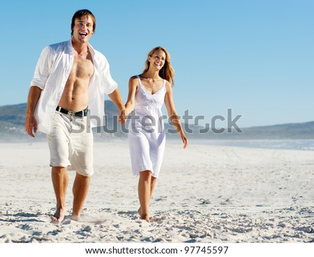 romantic honeymoon couple walk on the beach during a tropical summer holiday vacation. carefree stress free lifestyle concept. - stock photo